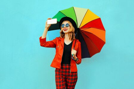 Happy smiling woman taking selfie picture by phone with colorful umbrella in red jacket, black hat on blue wall background