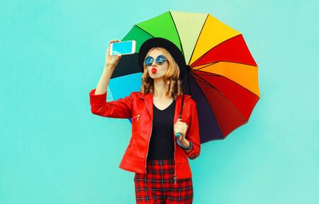 Young woman taking selfie picture by smartphone blowing red lips sending sweet air kiss with colorful umbrella in red jacket, black hat on blue wall background