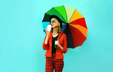 Portrait woman drinking coffee holding colorful umbrella in red jacket, black hat on blue wall background