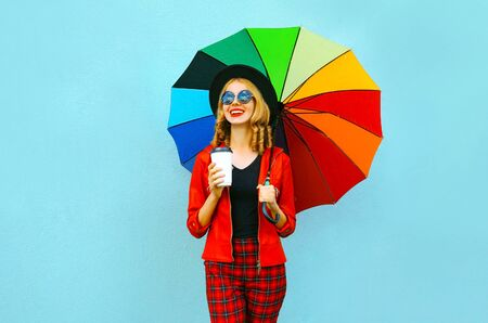 Portrait smiling woman holding colorful umbrella, hot coffee cup, wearing red jacket, black hat on blue wall background