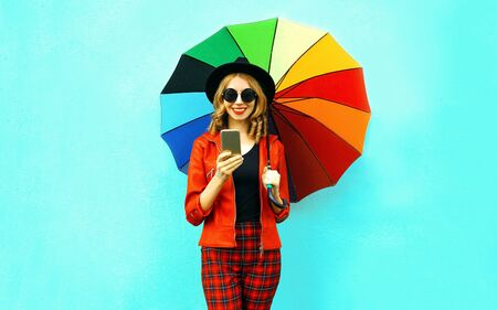 Portrait smiling young woman holding phone with colorful umbrella in red jacket, black hat on blue wall background Stock Photo