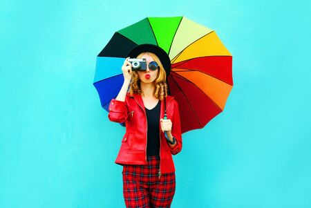 Young woman holding colorful umbrella, retro camera taking picture in red jacket, black hat on blue wall background