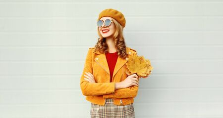 portrait smiling woman with yellow maple leaves wearing orange french beret on city street over gray wall background Фото со стока