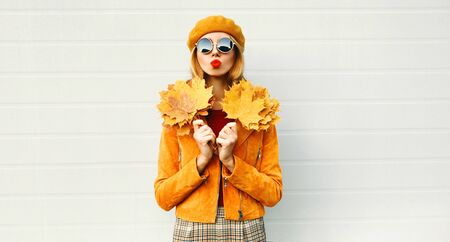 Autumn portrait woman holding yellow maple leaves blowing red lips sending sweet air kiss in french beret posing over gray wall background Stok Fotoğraf - 132051378