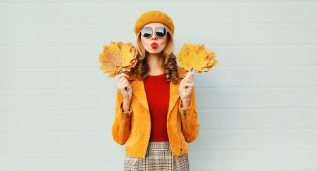 Autumn portrait woman holding yellow maple leaves blowing red lips sending sweet air kiss in french beret posing over gray wall background Stok Fotoğraf