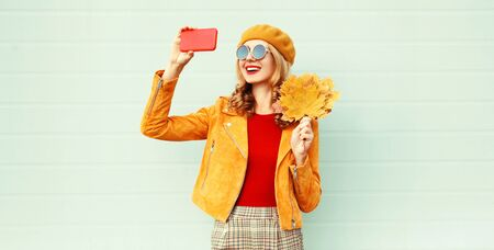 Autumn smiling woman taking selfie picture by phone holding yellow maple leaves wearing french beret hat posing on city street over gray wall background Фото со стока