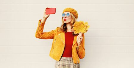 Autumn mood! woman taking selfie picture by phone blowing red lips sending sweet air kiss holding yellow maple leaves wearing french beret hat posing on city street over gray wall background Stock Photo