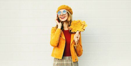 Autumn portrait smiling woman calling on phone holding yellow maple leaves wearing french beret on city street over gray wall background