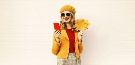 Autumn portrait smiling woman holding phone, yellow maple leaves wearing french beret on city street over gray wall background