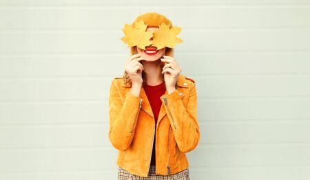 Autumn mood! happy smiling woman holding in her hands yellow maple leaves hiding her eyes over gray wall background Фото со стока