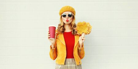 Autumn portrait woman with yellow maple leaves, coffee cup blowing red lips sending sweet air kiss over gray wall background Stok Fotoğraf