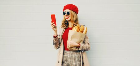 Portrait beautiful smiling woman holding phone, grocery shopping paper bag with long white bread wearing red beret over blank gray wall background Stock Photo