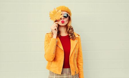Autumn portrait woman holding in her hands yellow maple leaves hiding her eye, girl blowing red lips sending sweet air kiss over gray wall background Stok Fotoğraf