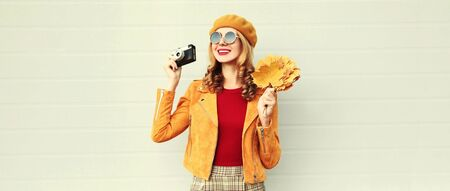 Autumn portrait happy smiling woman holding yellow maple leaves and camera wearing french beret, jacket over gray wall background Imagens