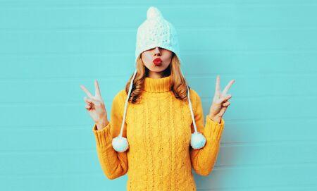 Portrait d'hiver cool jeune femme s'amusant tire un chapeau sur ses yeux portant un pull en tricot jaune et un chapeau blanc avec pompon, femme soufflant des lèvres rouges faisant un baiser d'air sur fond de mur bleu