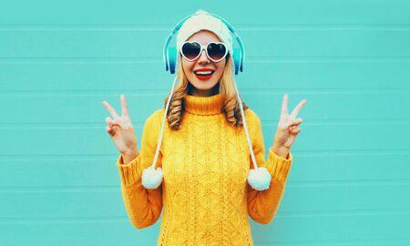 Winter portret gelukkig lachende jonge vrouw in draadloze koptelefoon luisteren naar muziek dragen gele gebreide trui en witte muts met pom pom, hartvormige zonnebril op blauwe muur achtergrond