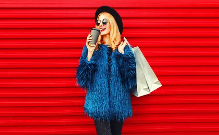 Retrato elegante mujer sonriente tomando café sosteniendo bolsas de compras vistiendo abrigo de piel sintética azul, sombrero redondo negro y gafas de sol posando sobre fondo de pared roja