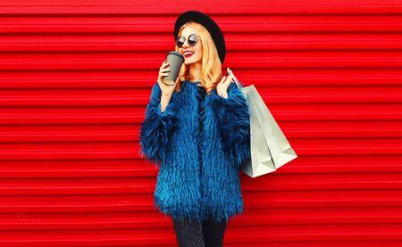 Ritratto elegante donna sorridente che beve caffè con in mano le borse della spesa indossando un cappotto di pelliccia sintetica blu, cappello tondo nero e occhiali da sole in posa su sfondo rosso muro