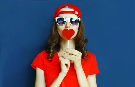 Portrait cool young woman with heart shaped red lollipop blowing red lips sending sweet air kiss wearing baseball cap, sunglasses over blue background Stok Fotoğraf