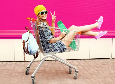 cool young smiling woman having fun sitting in trolley cart with skateboard over colorful pink background