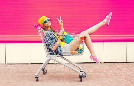 coole junge lächelnde frau, die spaß hat, im wagen mit skateboard über buntem rosa hintergrund zu sitzen