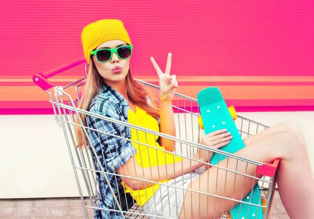 cool young smiling woman having fun sitting in trolley cart with skateboard over colorful pink background Foto de archivo