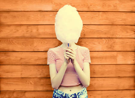 Cheerful young woman having fun covering her face with cotton candy in amusement park on wooden wall background Stok Fotoğraf - 150597433
