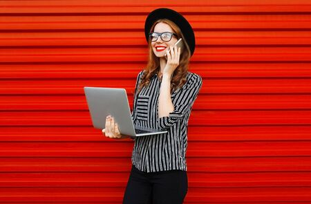 Modern young woman calling on smartphone with laptop on red wall background Stok Fotoğraf - 150540324