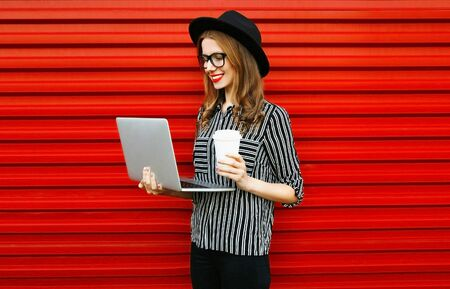 young woman working with laptop drinking coffee or tea on red wall background Stok Fotoğraf - 150540328