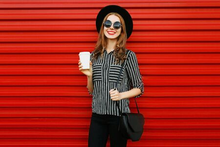 Stylish young woman with coffee cup wearing a black white striped shirt, round hat and handbag clutch on city street over red wall background