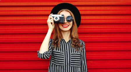 Portrait young woman photographer with vintage film camera over red wall background Stok Fotoğraf - 150540341