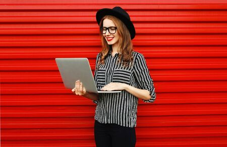 Caucasian young woman working with laptop on red wall background Stok Fotoğraf - 150540345