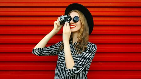 Portrait young woman photographer with vintage film camera over red wall background Stok Fotoğraf - 150540348