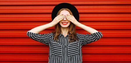 Portrait of smiling young woman covering her eyes with her hands wearing a black round hat, white striped shirt on red wall background Stok Fotoğraf - 150540349