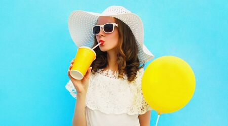 Portrait beautiful young woman drinking fresh juice with yellow balloon wearing a summer straw hat on blue background Stok Fotoğraf - 150563306