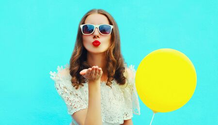Portrait of attractive young woman blowing red lips sending sweet air kiss with yellow balloon on blue background Stok Fotoğraf - 150563325