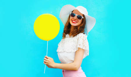Portrait happy smiling young woman with yellow balloon having fun wearing a summer straw hat on blue background
