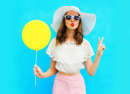Portrait of attractive young woman blowing red lips sending sweet air kiss with yellow balloon wearing a summer straw hat on blue background