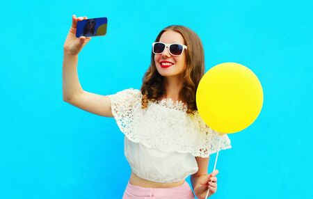 Happy smiling young woman with yellow balloon taking selfie picture by smartphone on blue background Stok Fotoğraf - 150563521