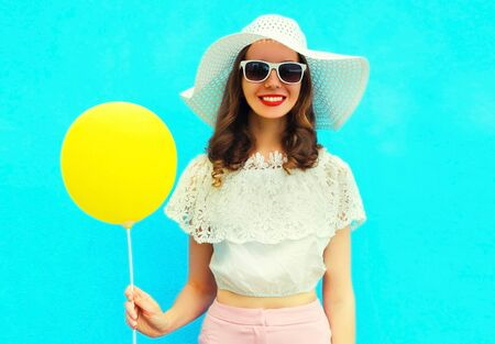 Portrait happy smiling young woman with yellow balloon having fun wearing a summer straw hat on blue background Stok Fotoğraf - 150563298