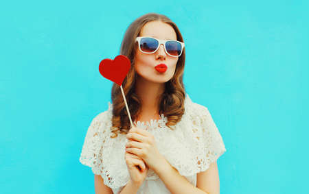 Portrait beautiful young woman with red heart shaped lollipop blowing lips sending sweet air kiss on blue background