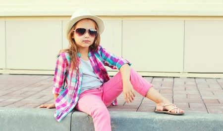 Little girl child wearing a summer straw hat, pink plaid shirt on city street Stok Fotoğraf - 152422752