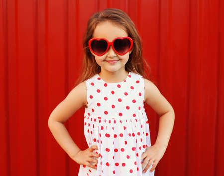 Portrait happy smiling little girl child wearing a white dress and red heart shaped sunglasses on background Stok Fotoğraf - 152422753
