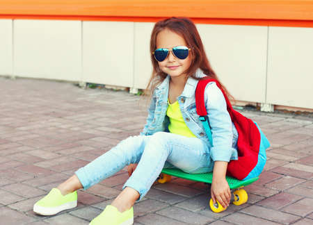 Portrait of little girl child sitting on skateboard with backpack on city street
