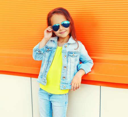 Portrait of little girl child wearing a sunglasses, jeans jacket on city street over orange background Stok Fotoğraf
