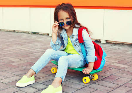 Portrait of little girl child sitting on skateboard with backpack on city street Stok Fotoğraf - 152422888