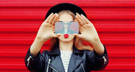 Close-up woman taking selfie picture by smartphone over wall background Stok Fotoğraf - 152443459