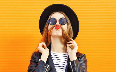 Portrait close up young woman showing mustache her hair blowing red lips having fun wearing a black round hat over orange wall background Stok Fotoğraf - 152443502