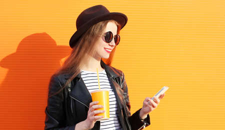 Close up portrait smiling young woman with cup of juice looking at phone over orange wall background Stok Fotoğraf - 152665862