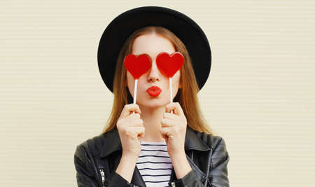 Close up portrait young woman covering her eyes with red heart shaped lollipop blowing lips sending sweet air kiss Stok Fotoğraf - 152665865